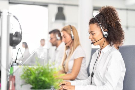 Foto de Call center worker accompanied by her team. Smiling customer support operator at work. Young employee working with a headset. - Imagen libre de derechos
