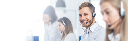 Photo for Call center worker accompanied by his team. Smiling customer support operator at work. Young employee working with a headset. - Royalty Free Image