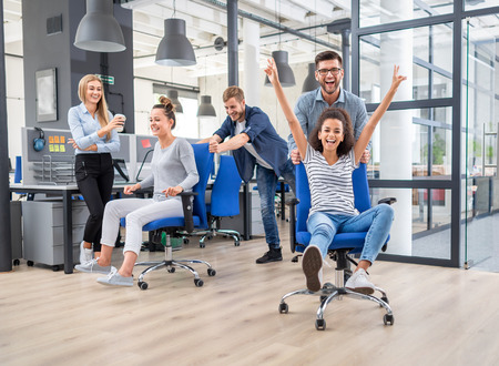 Photo for Young cheerful business people dressed in casual clothing are having fun on rowing chairs in a modern office. Happy team concept. - Royalty Free Image