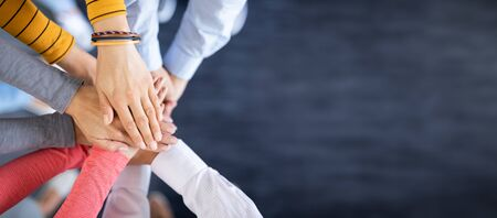 Photo pour Close up top view of young business people putting their hands together. Stack of hands. Unity and teamwork concept. - image libre de droit