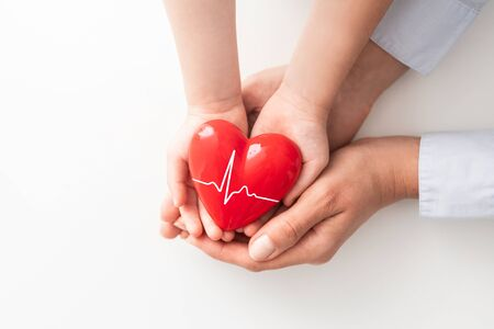 Foto de An adult, mother and child hold a red heart in their hands. Concept for charity, health insurance, love, international cardiology day. - Imagen libre de derechos