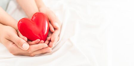 Photo pour An adult, mother and child hold a red heart in their hands. Concept for charity, health insurance, love, international cardiology day. - image libre de droit