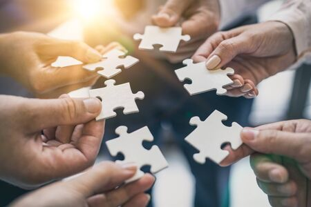 Foto de A group of business people assembling jigsaw puzzle. The concept of cooperation, teamwork, help and support in business. - Imagen libre de derechos