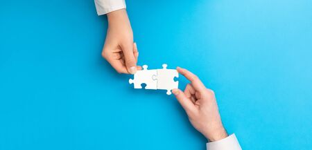 Photo pour The man and woman holds in hand a jigsaw puzzle. Business solutions, success and strategy concept. - image libre de droit