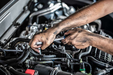 Photo pour Auto mechanic working and repair on car engine in mechanics garage. Car service. Man with wrench at workshop. - image libre de droit