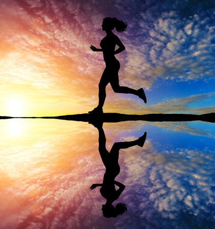 Photo pour Girl running at sunset with reflection in water - image libre de droit