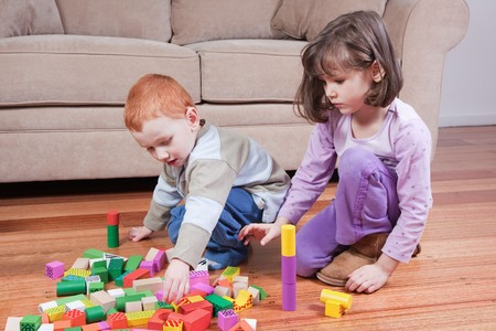 Two kids playing with blocks in front of couch