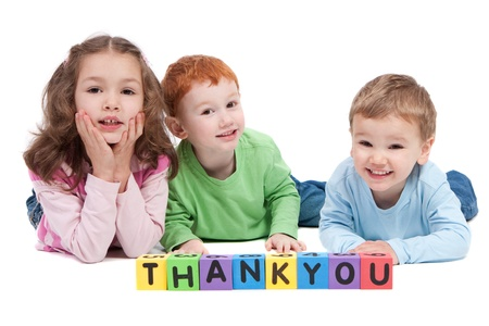 Three children lying with saying thankyou with kids letter blocks. Isolated on white.