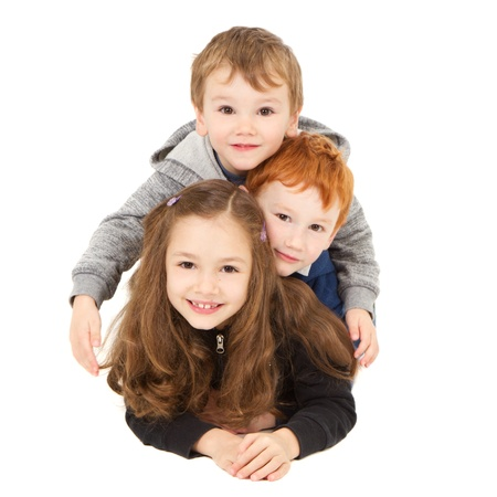 Photo pour Three happy children laying down in pile  Isolated on white  - image libre de droit