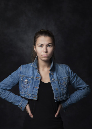 Charismatic young woman in a denim suit on a dark background