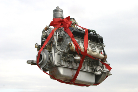 Photo pour A gift in the form of a truck engine decorated with fresh flowers is floating in the sky against a background of clouds. - image libre de droit