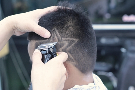 The boy's haircut with clipper and razor in the barber shop