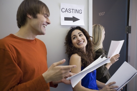 Three people in line at casting call. Horizontally framed shot.