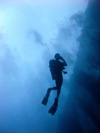 scuba diver from below in  blue sea
