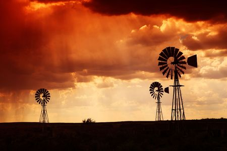Brewing thunderstorm in the dessert area of the Karoo in South Africa just before sunset. Three wind pumps silhouetted against the skyline with sunbeams shining through the clouds.の写真素材