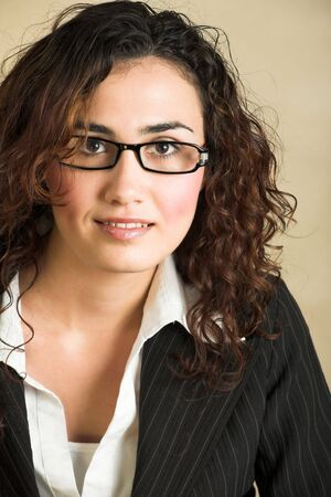 Portrait of a beautiful young adult Caucasian businesswoman with light skin and curly brown hair, brown eyes and pink lips, wearing a pinstripe Jacket and white shirt with spectacles