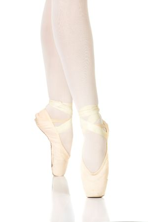 Young female ballet dancer showing various classic ballet feet positions on Pointe against a white background - 4th position en pointe. NOT ISOLATED