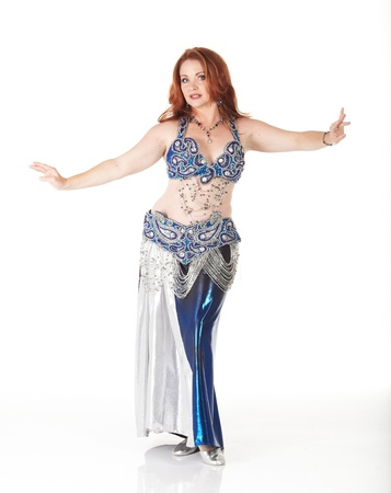 Lithe adult caucasian belly dancer with red hair and a blue belly dancing outfit performing steps on a white background. Not Isolated
