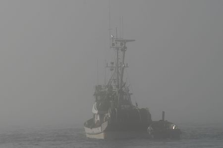 A fishing boat disappearing into deep fog while looking for fish in the Puget Sound.