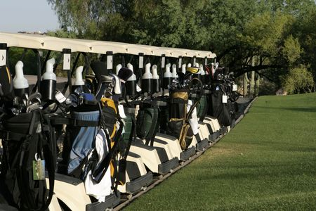A row of golf carts are lined up at the starting area and are ready to start the day's round with a shotgun start tournament. The carts are loaded in the back with a variety of golf clubs and golf bags.