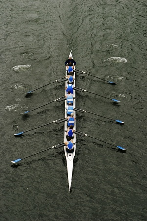 An eight person shell with a coxswain rowing in races on Lake Washington. As they row in unison, the boat cuts through the water.