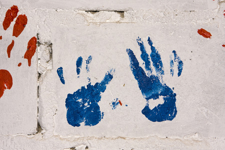 A pair of blue and red handprints on a white concrete wall make a colorful display on a preschool wall in a township in South Africa.