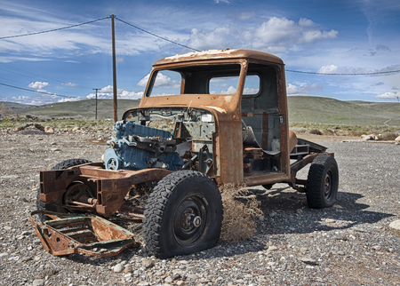 A solitary old pickup truck, abandoned in a gravel parking lot and exposed to the elements in Eastern Washington, is rusting while being scavenged for parts.