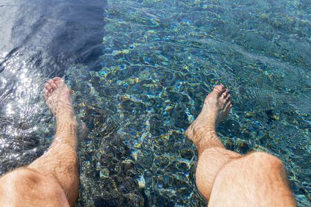 Personal perspective man legs dangling in the swimming pool