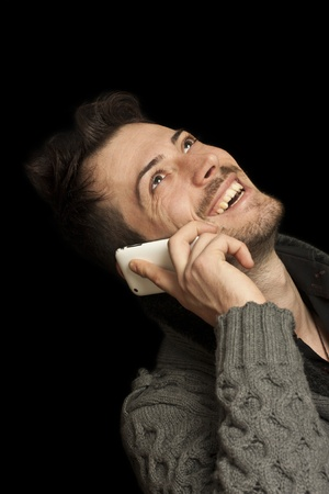 Portrait of casual man talking on mobile phone. Isolated on black