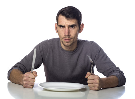 Man at dinner table with fork and knife raised. Hunger strike isolated over white background