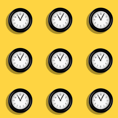 Foto de A Classic hand clocks pattern on yellow background. Time passing concept with clock pointing at 11 in the morning. - Imagen libre de derechos