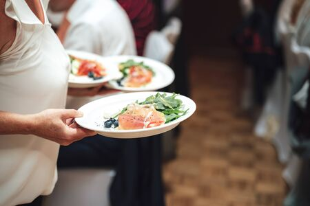 Photo pour Woman carrying white plates with light snack. Slices of ham, garden rocket and blueberries. Celebration, party, birthday or wedding concept. - image libre de droit