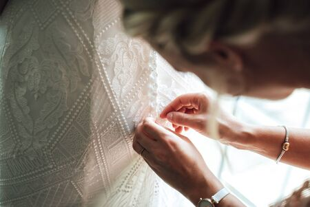 Photo pour Bridesmaid helping bride to dress wedding gown. Close up of hands fastening buttons on lace wedding dress. Wedding day concept. - image libre de droit