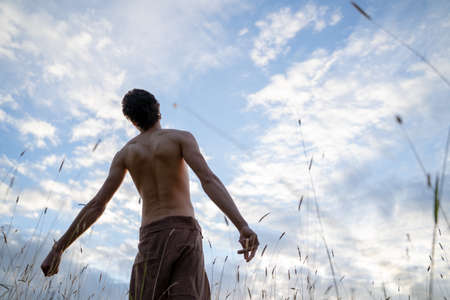 Photo pour Low angle rear view of shirtless man standing against cloudy sky in forest - image libre de droit