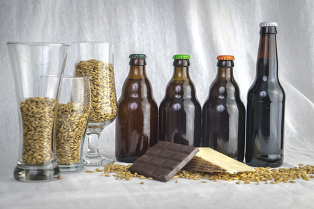 Set of beer bottle with barley chocolate bar and grain on white background