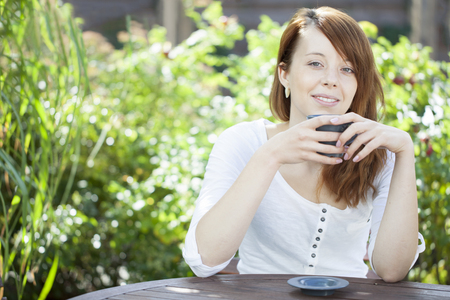 Young woman relaxing outdoors on a garden patio against lush green leaves with a mug of coffee or tea in her hands looking at the camera with a smile