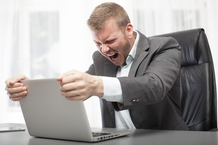 Angry Businessman Shaking His Laptop Computer And Yelling In