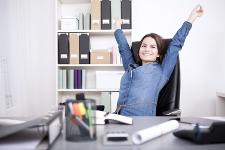 Foto de Happy Young Office Woman Sitting on her Chair Stretching her Arms While Looking at the Camera. - Imagen libre de derechos