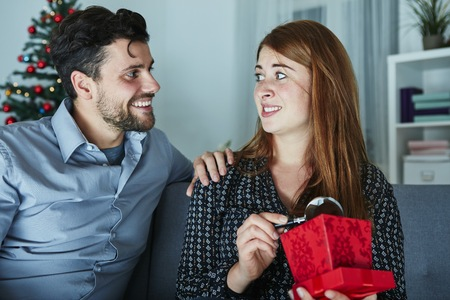 girlfriend looks sceptical to her christmas gift with magnifier