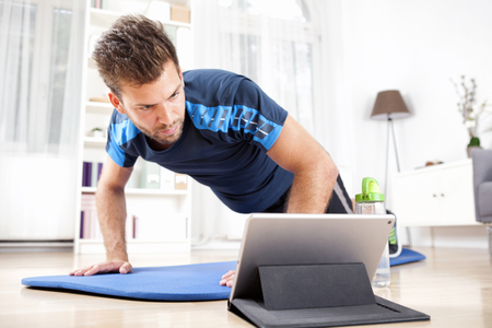 Athletic Young Man Doing a Planking Exercise at Home While Watching Movie on his Tablet Computer.