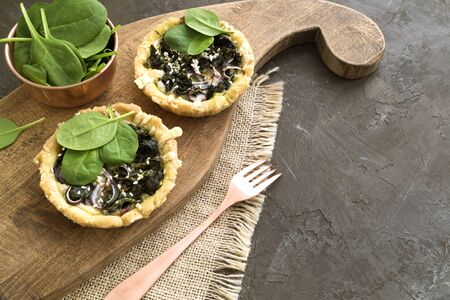 Cakes with spinach on a wooden Board.
