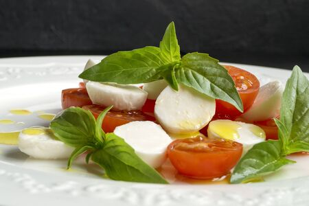 Photo pour Caprese salad with ripe tomatoes and mozzarella with fresh Basil leaves. Italian food. - image libre de droit