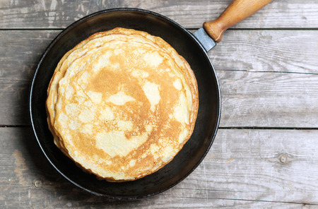 Stack of pancakes on a cast-iron frying pan. Top view