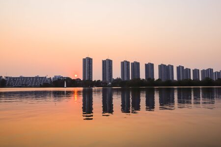 Photo pour CItyscape modern apartment building near a lake under sunset twilight with cloud sky background with water reflections for background. - image libre de droit