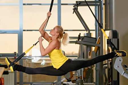 Young attractive woman does splits crossfit stretching with trx fitness straps in the gyms studio