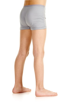 Barefoot young boy in underwear standing on white background