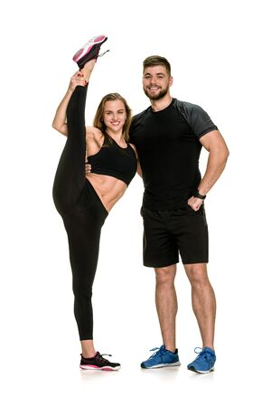 Photo for Young fit man helping flexible woman to stretch her leg - Royalty Free Image
