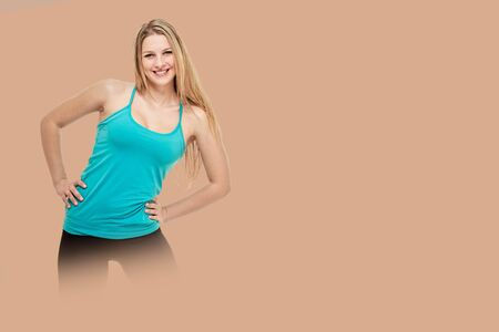 Cheerfully smiling woman doing exercise , isolated on background salmon shade redの写真素材