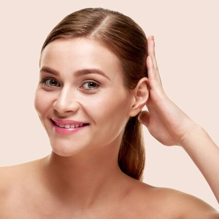 Photo pour Attractive smiling woman touching her healthy shiny hair, on light color background - image libre de droit