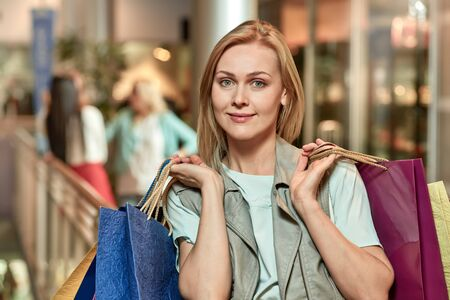 Photo pour Happy smiling woman with colorful bags and her friends doing shopping - image libre de droit